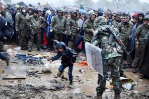 Un niño cruza del pueblo griego de Idomeni al sur de Macedonia mientras otros refugiados e inmigrantes esperan para pasar el jueves 10 de septiembre de 2015. Miles de personas desafiaron las fuertes lluvias para tratar de llegar a otros países de Europa. (Foto AP/Giannis Papanikos)
